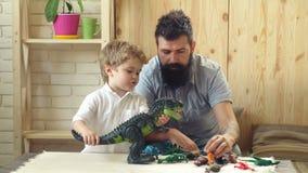 Игра отца и сына с динозаврами Прелестные маленькие детские игры с его бородатым отцом с пластиковыми динозаврами отец сток-видео