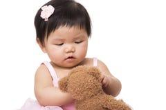 Игра ребёнка Азии с куклой Стоковое Изображение