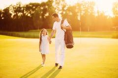 Игра семьи гольфа Отец и дочь идут вдоль поля для гольфа принимая их руки на заходе солнца Стоковые Изображения