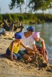 Игра семьи и строит замок песка на пляже Праздник и концепция перемещения Стоковое фото RF