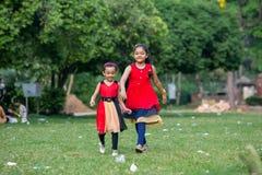 Игра 2 сестер с красным платьем в земле стоковая фотография rf