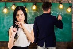 Игра студента девушки с eyeglasses пока учитель пишет на доске Дама на мечтательном внимании оплаты стороны не к учителю Стоковое Фото