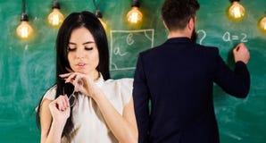Игра студента девушки с eyeglasses пока учитель пишет на доске Студент с длинными волосами в официально носке смотрит Стоковое Фото