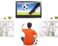 Игра футбола молодого вентилятора наблюдая дома Стоковая Фотография