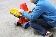 Игра ` s ребенка с песком Стоковая Фотография