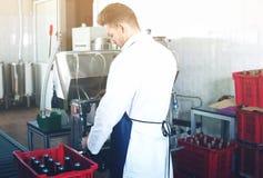 Игристое вино работника разливая по бутылкам с машиной Стоковое Изображение