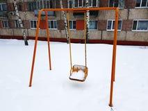 Игровая площадка около дома в зиме - качании стоковое фото rf