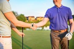Игроки в гольф трясут руки друг с другом стоковая фотография rf