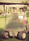 Игроки в гольф человека и женщины ехать тележка гольфа Стоковое Изображение