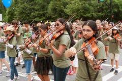 Игроки скрипки молодости выполняют пока идущ в старых солдатах проходят парадом Стоковое фото RF