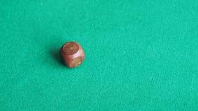Игрок бросает деревянную кость одно два раза на зеленой таблице акции видеоматериалы