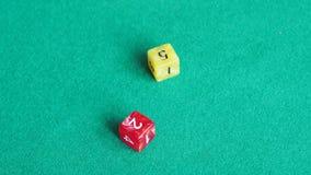 Игрок бросает красное и желтый dices четыре раза на зеленой доске видеоматериал