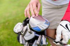 Игрок в гольф выбирая самый лучший клуб стоковые изображения rf
