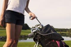 Игрок в гольф девушки принимая вне утюг от мешка гольфа. Стоковые Фотографии RF