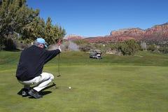 игрок в гольф его putt подкладки Стоковые Фотографии RF