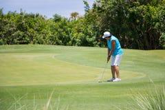 Игрок в гольф кладя шарик на зеленый цвет Стоковые Изображения