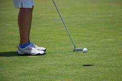 Игрок в гольф кладя шарик на зеленый цвет Стоковое Изображение