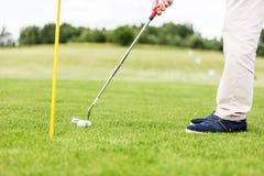 Игрок в гольф кладя шарик в отверстие на поле для гольфа Стоковая Фотография