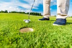 Игрок в гольф кладя шарик в отверстие на поле для гольфа Стоковое Изображение RF