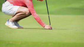 Игрок в гольф кладя шар для игры в гольф на зеленую траву для прохода проверки для того чтобы продырявить стоковые фото