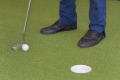 Игрок в гольф кладя шар для игры в гольф на зеленый гольф Стоковое фото RF
