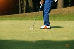 Игрок в гольф кладя шар для игры в гольф на зеленый гольф Стоковые Изображения RF