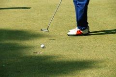 Игрок в гольф кладя шар для игры в гольф на зеленый гольф Стоковое Фото