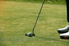 Игрок в гольф кладя шар для игры в гольф на зеленый гольф Стоковое Изображение RF