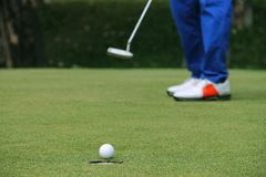 Игрок в гольф кладя шар для игры в гольф на зеленый гольф Стоковые Изображения