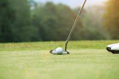 Игрок в гольф кладя шар для игры в гольф на зеленый гольф стоковое изображение