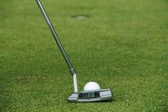 Игрок в гольф кладя шар для игры в гольф на зеленый гольф Стоковые Фото