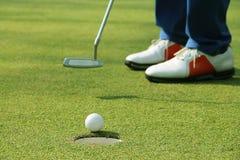 Игрок в гольф кладя шар для игры в гольф на зеленый гольф Стоковая Фотография RF