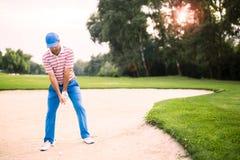 Игрок в гольф принимая съемку бункера стоковые изображения rf