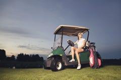 Игрок в гольф сидя в тележке гольфа на сумерк. стоковое изображение