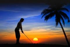 Игрок в гольф силуэта на заходе солнца Стоковые Фотографии RF