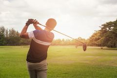 Игрок в гольф ударяя съемку гольфа с клубом на курсе на времени вечера стоковые изображения rf