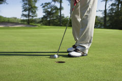 Игрок в гольф выстукивает внутри с короткой клюшкой на зеленом цвете с деревьями около озера Стоковая Фотография