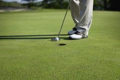 Игрок в гольф выстукивая вкратце удар, загоняющий мяч в лунку Стоковое Изображение