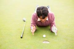 Игрок в гольф лежа около шара для игры в гольф Стоковые Изображения
