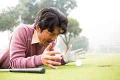 Игрок в гольф лежа около шара для игры в гольф Стоковые Фото