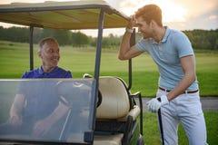 Игрок в гольф около тележки гольфа Стоковое Изображение RF
