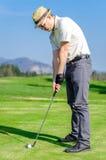 Игрок в гольф откалывает шар для игры в гольф на зеленый цвет с гольфом c водителя Стоковая Фотография RF