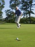 Игрок в гольф празднует удар, загоняющий мяч в лунку на зеленом цвете Стоковая Фотография