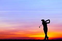 Игрок в гольф силуэта играя гольф на красивом заходе солнца Стоковое Изображение RF