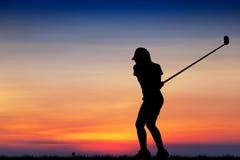 Игрок в гольф силуэта играя гольф на красивом заходе солнца Стоковые Фотографии RF