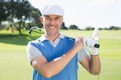 Игрок в гольф стоя и отбрасывая его клуб усмехаясь на камере стоковое фото