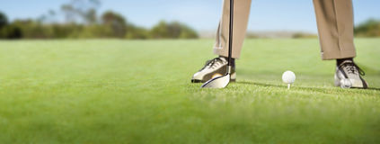 Игрок в гольф устанавливая шар для игры в гольф на тройнике Стоковое Изображение