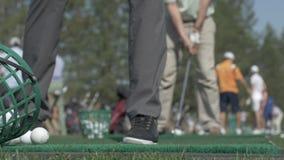 Игрок в гольф ударяя шарик с клубом на красивом поле для гольфа Игрок в гольф ударяет проход снятый к дому клуба Ударять человека видеоматериал
