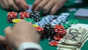 Игрок в покер имеет выигрывая карточки комбинацию, держит пари все наличные деньги и свойство, безумные акции видеоматериалы