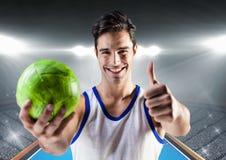 Игрок держа гандбол и показывая большие пальцы руки вверх против стадиона в предпосылке Стоковое Изображение RF